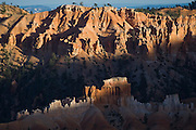 Sunset light selectively illuminates colorful sandstone hoodoos in Bryce Canyon National Park, Utah.