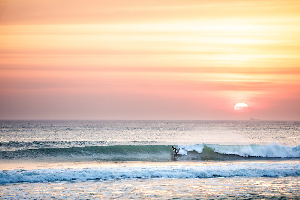 Surfer catching a wave at sunset under a pink winter sky, at the popular surfing beach, St Ouen's Bay, in Jersey, Channel Islands