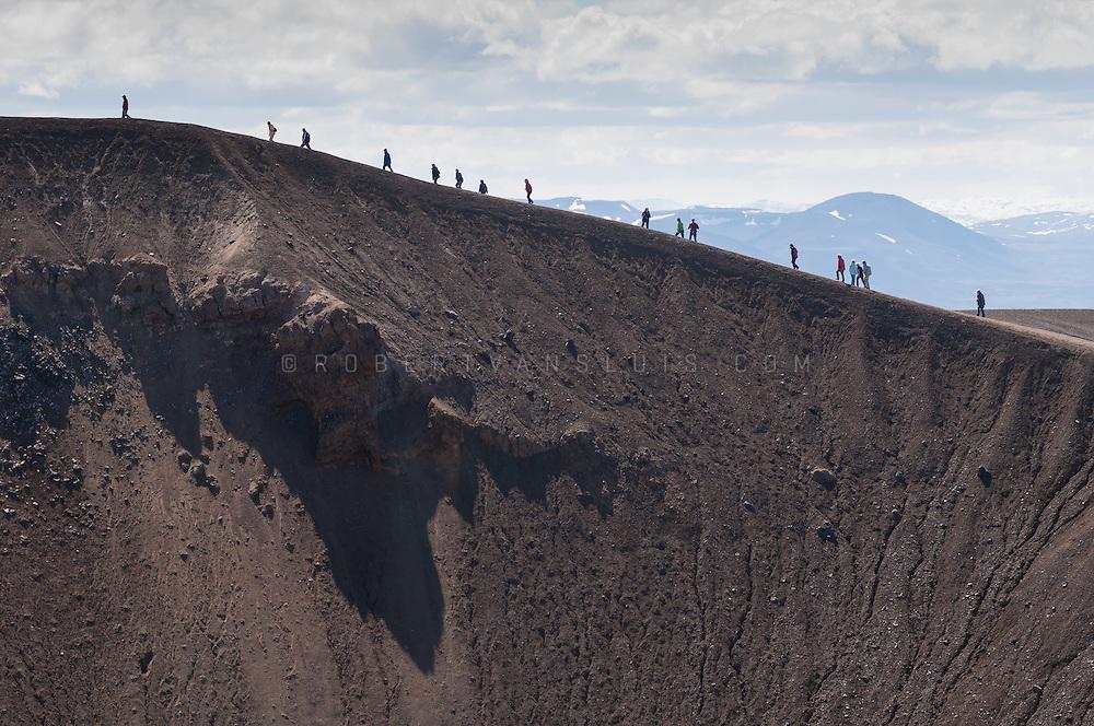 Tourists hiking the rim of the Viti crater, Krafla, Iceland