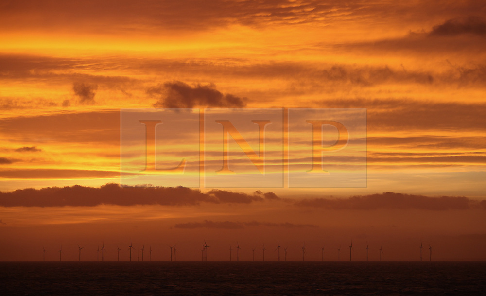 © Licensed to London News Pictures. 20/03/2014. North Wales, UK. An orange sky at dawn over the Rhyl Flats Offshore Wind Farm in North Wales this morning, 20th March 2014. Photo credit : Rob Arnold/LNP