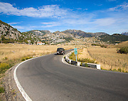 Vehicle driving around corner in rural road in Sierra de Grazalema natural park, Cadiz province, Spain