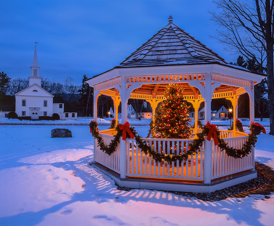 Gazebo in village green, with Christmas tree lit up at dusk, distant church, Hebron, NH