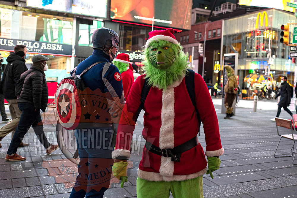 The Grinch attempts to stop tourists for a photo opportunity in Times Square for the Holiday season during the Coronavirus (Covid-19) outbreak in Manhattan,New York on Sunday, December 6, 2020. (Alex Menendez via AP)