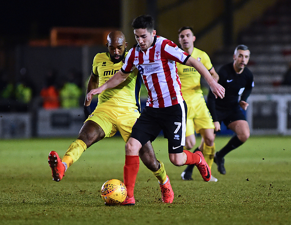 Lincoln City's Tom Pett vies for possession with Cheltenham Town's Nigel Atangana<br /> <br /> Photographer Andrew Vaughan/CameraSport<br /> <br /> The EFL Sky Bet League Two - Cambridge United v Lincoln City - Friday 9th February 2018 - Abbey Stadium - Cambridge<br /> <br /> World Copyright © 2018 CameraSport. All rights reserved. 43 Linden Ave. Countesthorpe. Leicester. England. LE8 5PG - Tel: +44 (0) 116 277 4147 - admin@camerasport.com - www.camerasport.com