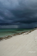 summer rain squall approaches beach lined with beach rock ( beach rock is a natural sedimentary rock which forms in the intertidal zone; the Atlantis Road in Bimini consists of subsided beach rock ) Sandy Point, Great Abaco, Abaco Islands, Bahamas ( Western Atlantic Ocean )