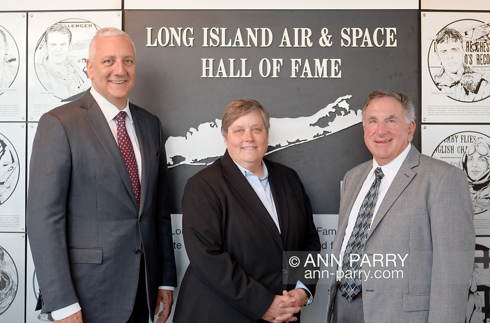 Garden City, NY, USA. June 21, 2018. Astronaut MIKE MASSIMINO; and DEBORAH HENLEY, VP (Executive Editor of Newsday), representing inductee Alicia Patterson; and LOUIS MANCUSO JR, representing his parents, inductees Louis and Carol Mancuso, pose at Cradle of Aviation Museum during Long Island Air & Space Hall of Fame Class of 2018 Induction.