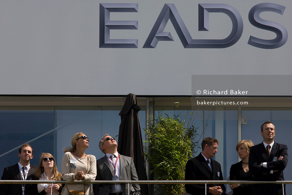 Guests admire aerobatic flying displays outside the EADS hospitality chalet at the Farnborough Air Show