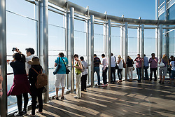 Tourists looking out over Dubai from At The Top Observation deck in Burj Khalifa the tallest structure in the world in Dubai United Arab Emirates UAE