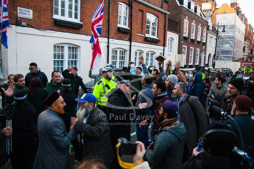 """Mayfair, London, November 28th 2014. A protest against Egypt's leader Al-Sisi descended into moinor scuffles as right wing """"patriots"""" from anti-Islamic group Britain First arrived to protest against the presence of Islamist preacher Anjem Choudary, who was recently arrestred as part of an ant-terror operation. Playing patriotic British Music, Britain First accused Muslims of worshiping a """"devil"""" and a """"paedophile prophet"""". Police had to intervene before hotheads on both sides became violent. PICTURED: Britain First Ant-Islamists on the left are kept apart from the Muslim anti-Sisi protesters."""