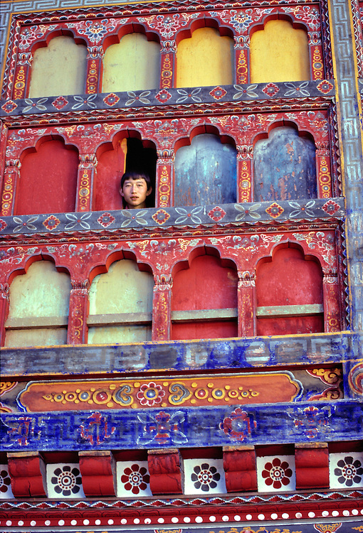 In Thimphu Dzong, Bhutan, a monk peers from a brightly painted bank of windows.
