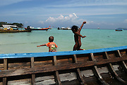 Thailand beach, two young local children playing in a fishing boat