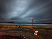 Evening storm breaks momentarily on the Australian coast at Mollymook  with street light and road crossing in foreground and streaking clouds in sky during long exposure. Licensing and Editions of 17