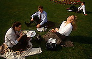 Three work colleagues enjoy a picnic on the grass in a City of London park in summer sunshine. As the male admires the body of the younger, more beautiful lady, she throws her head back as a reaction to the conversation. In the background are other office workers also relishing the warm weather in the capital.