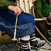 An elderly woman wearing traditional footwear (opinci) spins wool by hand outside her home, Botiza, Maramures, Romania. Traditionally subsistence farmers In Maramures raise their own sheep to provide wool for knitting and weaving clothing.