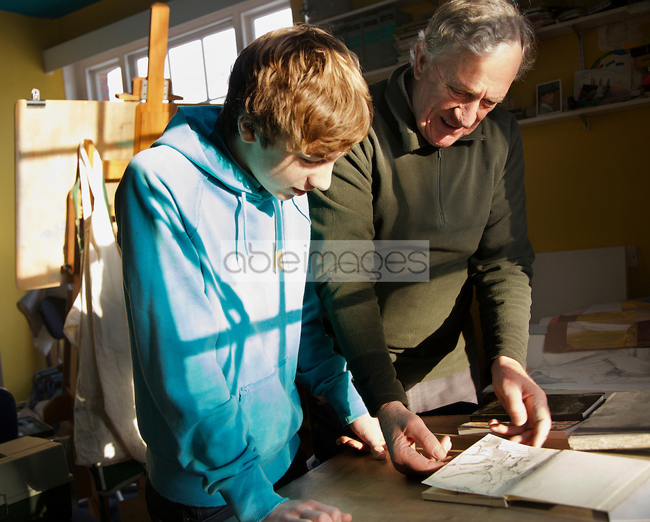 Grandfather showing grandson a drawing book
