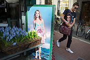 Photograph of a model in a summer dress interacting with passer by wearing an Elvis Presley t-shirt at the Stella McCartney flower stall on New Bond Street, London, UK.
