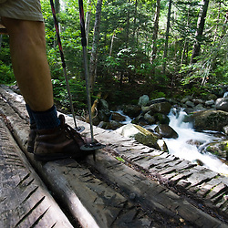 A hiker on a bridge over Gorge Brook in New Hampshire USA (MR)