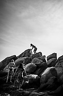 Black and white image of three young women traveling in Southeast Asia, here climbing a rocky outcrop at the beach on Mamutik Island in Kota Kinabalu, Sabah, Malaysia. (August 2019)