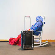 A commuter stranded at Charlotte-Douglas Airport sleeps in one of the iconic white rocking chairs.