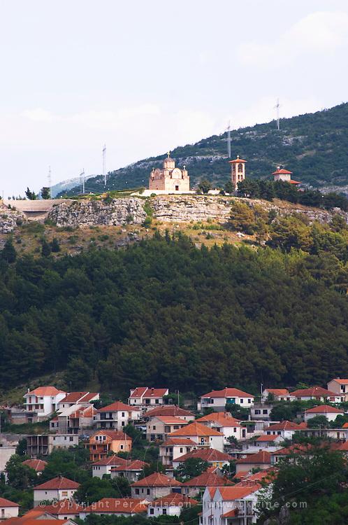 Houses. The monastery Gracanica on the historic hill known as Crkvina against a mountain backdrop. Trebinje. Republika Srpska. Bosnia Herzegovina, Europe.