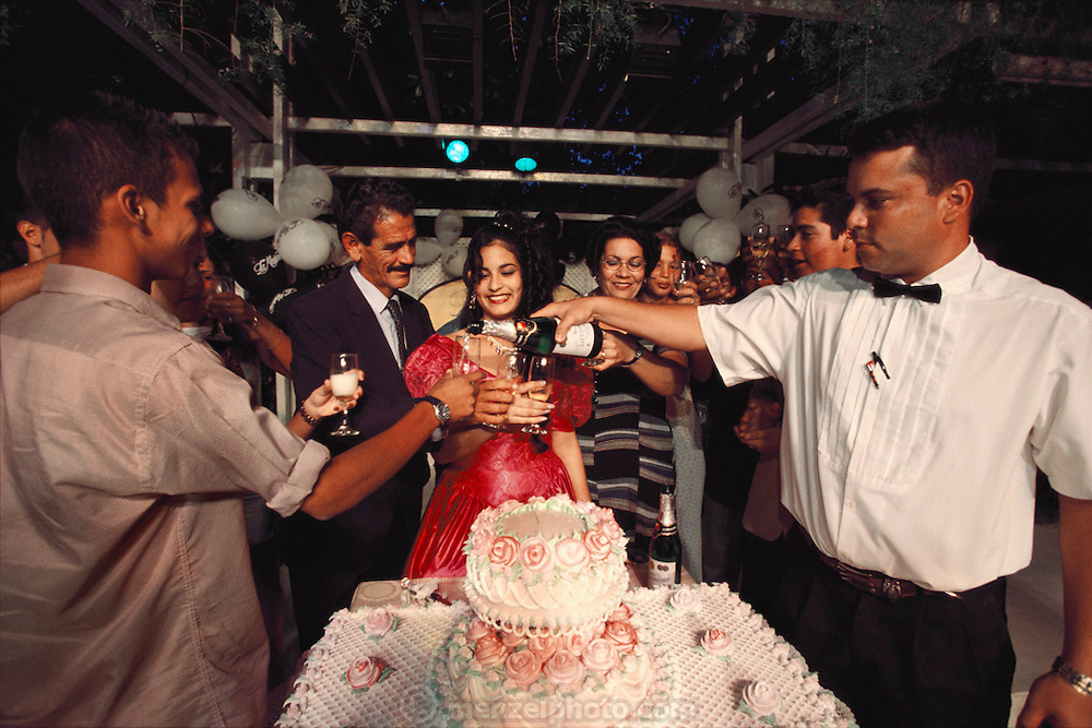 Iris Garcia Costa is toasted during her Quinceañera, or 15th Birthday, by her friends and parents (Montecristi Garcia, center left, and Eulina Costa, center right. The Quinceañera is the traditional coming-of-age party for 15-year-old girls in Cuba, and other Spanish speaking countries. From coverage of revisit to Material World Project family in Cuba, 2001.