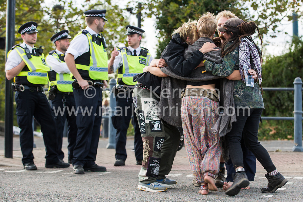 London, UK. 5 September, 2019. Metropolitan Police officers observe activists taking part in a Conference At The Gates (CATG) outside ExCel London on the fourth day of a week-long carnival of resistance against DSEI, the world's largest arms fair. The CATG involved a series of workshops themed around the arms trade in the context of state violence, with a particular focus on the issue of race.