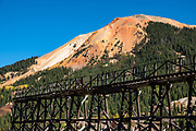 Ruins of Idarado Mine, north of Red Mountain Pass along the Million Dollar Highway, in Colorado, USA. Winding through the San Juan Mountains, the Million Dollar Highway is the scenic 25 miles of US Route 550 between Silverton and Ouray. It was named for the twelve miles south of Ouray through the Uncompahgre Gorge to the summit of Red Mountain Pass. As part of the San Juan Skyway Scenic Byway, the Million Dollar Highway twists along sheer cliff edges with hairpin curves and few guardrails, past spectacular yellow foliage colors in autumn.