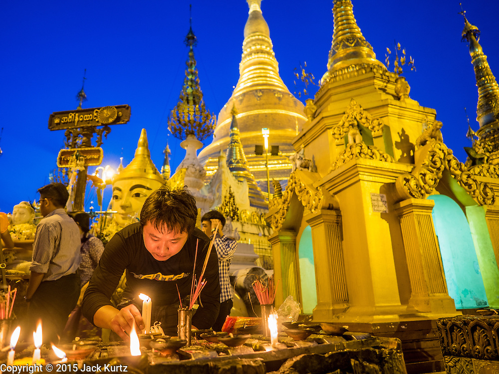 31 OCTOBER 2015 - YANGON, MYANMAR: Lighting candles and offering prayers as a form of merit making at Shwedagon Pagoda. Shwedagon Pagoda is officially known as Shwedagon Zedi Daw and is also called the Great Dagon Pagoda or the Golden Pagoda. It is a 99 metres (325ft) tall pagoda and stupa located in Yangon, Burma. The pagoda lies to the west of on Singuttara Hill, and dominates the skyline of the city. It is the most sacred Buddhist pagoda in Myanmar and contains relics of four past Buddhas: the staff of Kakusandha, the water filter of Koṇāgamana, a piece of the robe of Kassapa and eight strands of hair from Gautama, the historical Buddha. The pagoda was built between the 6th and 10th centuries by the Mon people, who used to dominate the area around what is now Yangon (Rangoon). The pagoda has been renovated numerous times through the centuries. Millions of Burmese and tens of thousands of tourists visit the pagoda every year, which is the most visited site in Yangon.      PHOTO BY JACK KURTZ