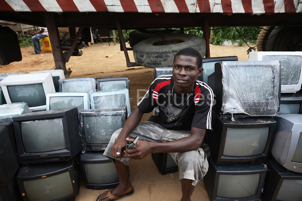 A labourer is resting amongst TVs which have all come from the UK. Alaba International Market is one of the largest markets for electronic goods in West Africa.  New and old - and a lot of non-working electronic goods such as TVs and computers come in to the market via Lagos harbour from the US, Western Europe and China. This picture is part of an undercover investigation by Greenpeace and Sky News.  A TV-set originally delivered to a municipality-run collecting point in UK for discarded electronic products was tracked and monitored by Greenpeace using a combination of GPS, GSM, and an onboard radiofrequency transmitter placed inside the TV-set.  The TV arrived in Lagos in container no 4629416 and was found in Alaba International Market and bought back by Greenpeace activist. The TV was subsequently brought back to England and used as proof of illegal export of electronic waste. A number of individual are currently on trial in London in connection with illegal exports(Nov 2011)