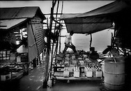 Man checks car batteries used by unnumerable boats in a makeshift waterfront shop on the the shore of Tonle Sap, Cambodia.