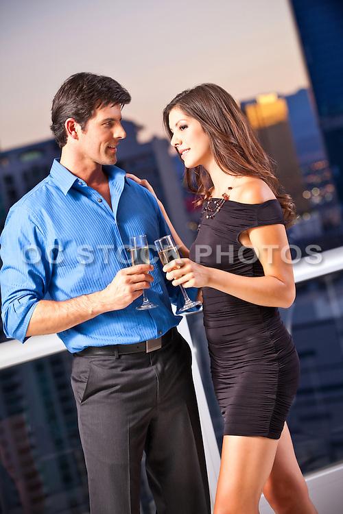 Romantic Couple Enjoying Happy Hour On A Balcony At Dusk