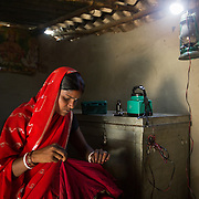 CAPTION: In the privacy of her otherwise extremely dark home, Seema Devi stitches under the light provided by the OORJAmitra device. LOCATION: Singhilpur, Saran District, Bihar, India. INDIVIDUAL(S) PHOTOGRAPHED: Seema Devi.