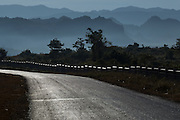 Sunlit road and fence with mountains, Hopone Township, Taunggyi
