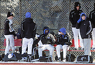 Chester, New York  - Mount Saint Mary College baseball players try to stay warm in the dugout with temperatures in the 30s during a baseball game against SUNY Brockport at The Rock Sports Park on Feb. 26, 2012.