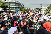 "03 DECEMBER 2013 - BANGKOK, THAILAND: Anti-government protestors mill around in the middle of a street before tearing down government barricades near the Metropolitan Police Bureau in Bangkok. Thousands of anti-government protestors entered the government offices in the Dusit district of Bangkok Tuesday after police stopped using tear gas and water cannons on the protestors. Protestors marched through the district waving Thai flags and chanting ""long live the King!"" Suthep Thaugsuban, leader of the protest movement, called it a partial victory but vowed to continue his battle to bring down the government of Yingluck Shinawatra.     PHOTO BY JACK KURTZ"