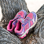 A pair of kid's shoes on a tree at the beach of Skala Sykamias, Lesvos, Greece.