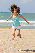 Israel, Tel Aviv, a preteen girl of 12 jumps on the shore