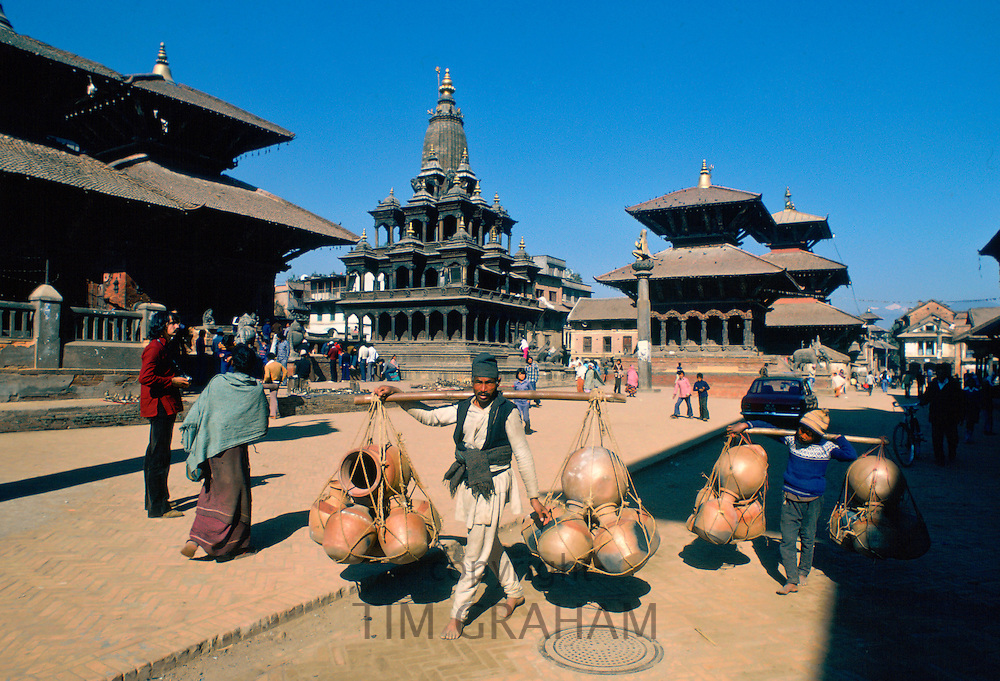 Man and boy carrying heavy pots on shoulder hoists, Patan, Nepal