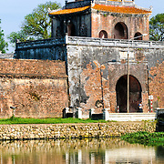 A man fishes in the waters of the moat surrounding the Imperial City in Hue, Vietnam. A self-enclosed and fortified palace, the complex includes the Purple Forbidden City, which was the inner sanctum of the imperial household, as well as temples, courtyards, gardens, and other buildings. Much of the Imperial City was damaged or destroyed during the Vietnam War. It is now designated as a UNESCO World Heritage site.
