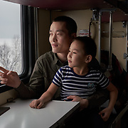 """Chinese tree logger WU Di travels on a Siberian train, holding a child he met on the train, in winter along the shore at Russia's Lake Baikal. Crowned the """"Jewel of Siberia"""", Baikal is the world's deepest lake, and the biggest lake by volume, holding 20% of the world's fresh water. In the winter, the lake 31,722 square meter surface is entirely frozen with ice averaging 2 meters thick."""