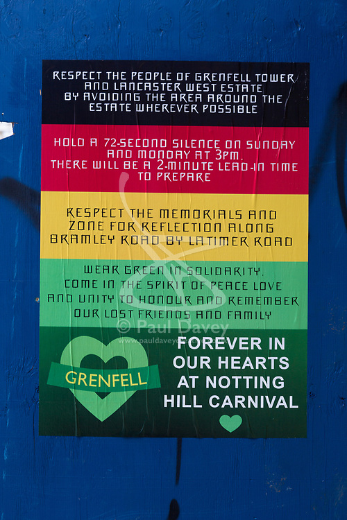 A poster advertises the times on both days of the carnival when a minute's silence will be held for the victims of the nearby Grenfell Tower fire disaster as shops and properties in the west London area of the Notting Hill Carnival prepare for the hundreds of thousands of revellers by erecting protective hoardings. London, August 24 2018.
