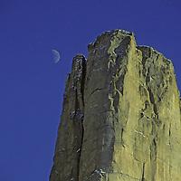 BAFFIN ISLAND, Nunavut, Canada. Moon over unnamed granite spire in the Stewart Valley.