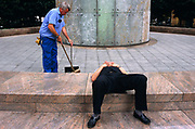 As a young office worker sleeps incongruously on a marble pavement, a street sweeper nearby brushes away litter with a small dustpan. The manual labourer wears blue overalls, yellow gloves and keys in his back pocket while the man in a wastecoat and smart trousers and polished slip-on shoes appears to be fast asleep, his fingers across his chest. This scene suggests the social divisions of the working man: Of the young, educated post-war generation whose opportunities have afforded them a faster lifestyle, far removed from that of the physically-demanding job of a man whose life has been spent cleaning and sweeping. English social differences is clearly represented here as the harshness of the manual labourer versus a lazy youth of today, seen in the middle of the modern city.