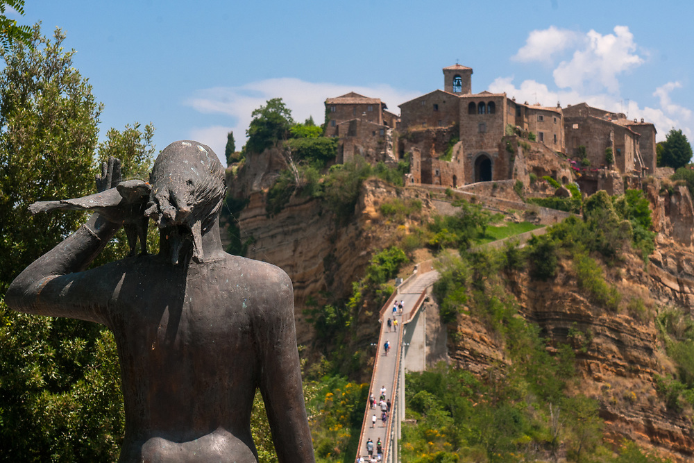 """A view of the village of Civita di Bagnoregio and of the statue before reaching the bridge to the town.<br /> Civita di Bagnoregio is a town in the Province of Viterbo in central Italy, a suburb of the comune of Bagnoregio, 1 kilometre (0.6 mi) east from it. It is about 120 kilometres (75 mi) north of Rome. Civita was founded by Etruscans more than 2,500 years ago. Bagnoregio continues as a small but prosperous town, while Civita became known in Italian as La città che muore (""""The Dying Town""""). Civita has only recently been experiencing a tourist revival. The population today varies from about 7 people in winter to more than 100 in summer.The town was placed on the World Monuments Fund's 2006 Watch List of the 100 Most Endangered Sites, because of threats it faces from erosion and unregulated tourism."""