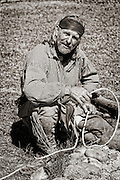 Mountain Man next to the fire burning the edges of a newly twisted rope. Photo taken at Historic Fort Bridger in Southern Wyoming.