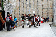 Group of men and women, dressed in traditional period costume, walk through the streets of Dubrovnik old town, Croatia