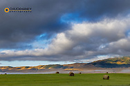 Hay bales in clearing fog with Salish Mountains in Lake County, Montana, USA