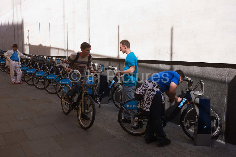 An elderly man watches younger males as they prepare to ride off on newly-rented 'Boris bikes' in Westminster, Central London. The sponsored bicycles have been provided for Londoners and visitors by Barclays Bank and is the brainchild of Mayor of London, Boris Johnson whose aim is to cut down on heavy traffic and increase cycling journeys. These Polish tourists have paid their deposit and are now about to ride off round central London.