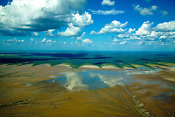 Wet season clouds reflect in water pooling on the mud flats that line the Kimberley coastline.  The mangrove forests create beautiful scalloped formations.