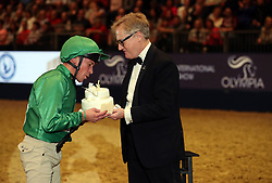 Frankie Dettori gets his birthday cake off Simon Brooks Ward after he competes in the Markel Champions Challenge in aid of the Injured Jockeys Fundduring day four of the London International Horse Show at London Olympia.